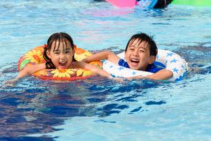 プールで浮き輪で遊ぶ女の子と男の子の写真素材 [FYI01569289]