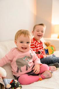 子供部屋のソファに座って遊ぶ男の子と女の子の写真素材 [FYI01569333]