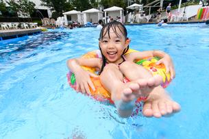 プールで浮き輪で遊ぶ女の子の写真素材 [FYI01569369]