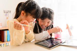 子供部屋でタブレットで遊ぶ女の子の写真素材 [FYI01569430]