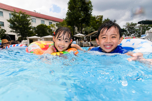プールで浮き輪で遊ぶ女の子と男の子の写真素材 [FYI01569546]