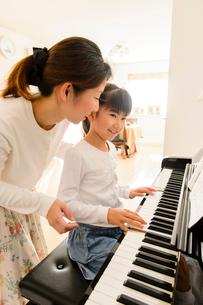 ピアノを弾く女の子と見守るお母さんの写真素材 [FYI01569566]