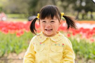 春の公園でチューリップ畑で遊ぶ女の子の写真素材 [FYI01569594]