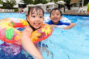プールで浮き輪で遊ぶ男の子と女の子の写真素材 [FYI01569659]