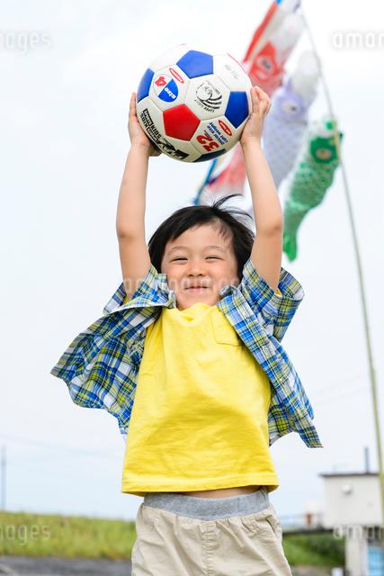 鯉のぼりをバックにサッカーボールで遊ぶ男の子の写真素材 [FYI01569662]