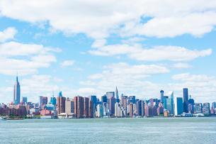 イーストリバーとマンハッタン高層ビル群の上に浮かぶ雲の写真素材 [FYI01569776]