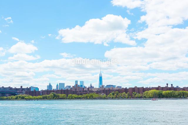イーストリバーとマンハッタン高層ビル群の上に浮かぶ雲の写真素材 [FYI01569794]