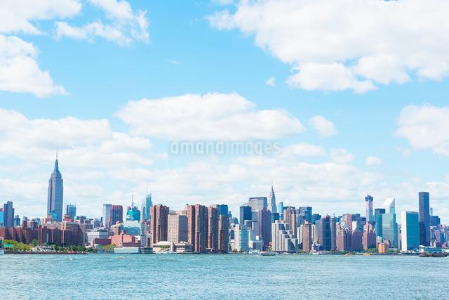 イーストリバーとマンハッタン高層ビル群の上に浮かぶ雲の写真素材 [FYI01569840]