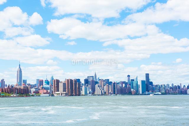 イーストリバーとマンハッタン高層ビル群の上に浮かぶ雲の写真素材 [FYI01569899]