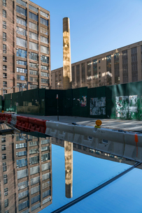 ハドソンヤード建設現場に置かれた外壁ウィンドーに映り込む煙突とビルの写真素材 [FYI01570089]