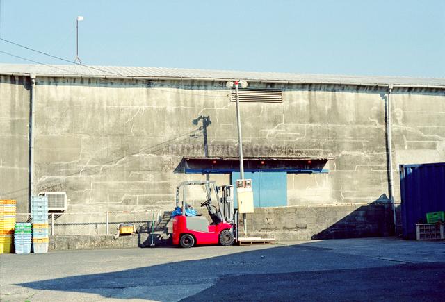 海岸倉庫と赤いフォークリフトの写真素材 [FYI01570505]