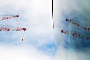 ビルのガラス窓に映ったふたつの建設クレーンの写真素材 [FYI01570590]
