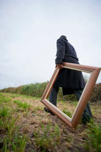 額縁を持って歩く日本人男性の写真素材 [FYI01570631]