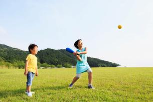 芝生の上で遊ぶ姉と弟の写真素材 [FYI01570740]