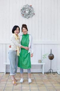 白壁の前に立つ2人の日本人女性の写真素材 [FYI01570843]