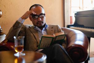 ソファで読書をする日本人男性の写真素材 [FYI01570987]