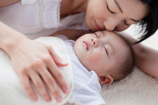 眠る赤ちゃんを見つめる母親の写真素材 [FYI01570994]