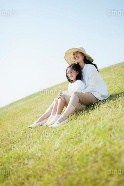 芝生に座る日本人の母と娘の写真素材 [FYI01571003]