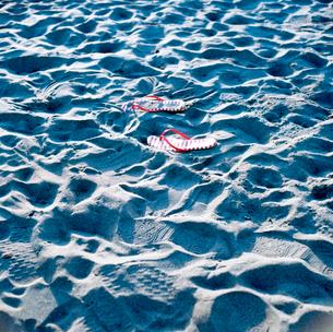 砂浜に脱ぎ置かれた女性用ビーチサンダルの写真素材 [FYI01571031]