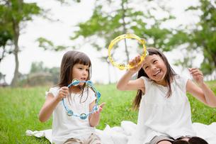 タンバリンで遊ぶハーフの姉妹の写真素材 [FYI01571044]