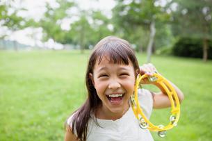 タンバリンで遊ぶハーフの女の子の写真素材 [FYI01571196]