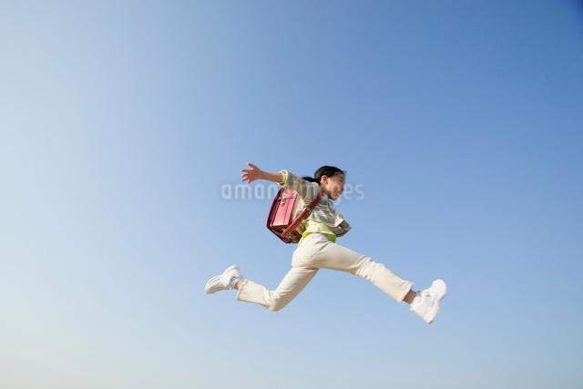 ジャンプする小学生の女の子の写真素材 [FYI01571228]