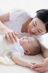 眠る赤ちゃんを見つめる母親の写真素材 [FYI01571257]