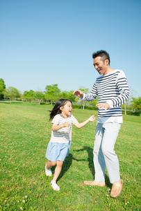 公園で遊ぶ父と娘の写真素材 [FYI01571499]