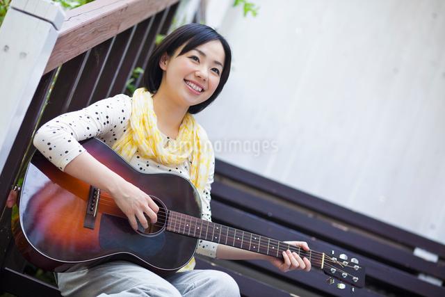 ギターを弾く日本人女性の写真素材 [FYI01571515]