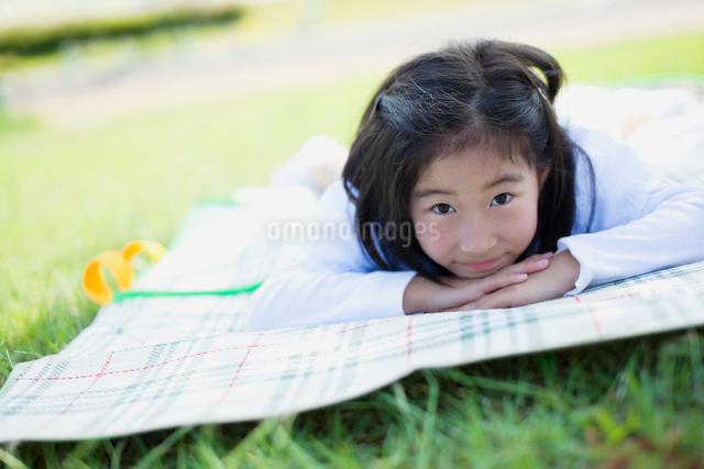 レジャーシートに寝転ぶ日本人の女の子の写真素材 [FYI01571522]