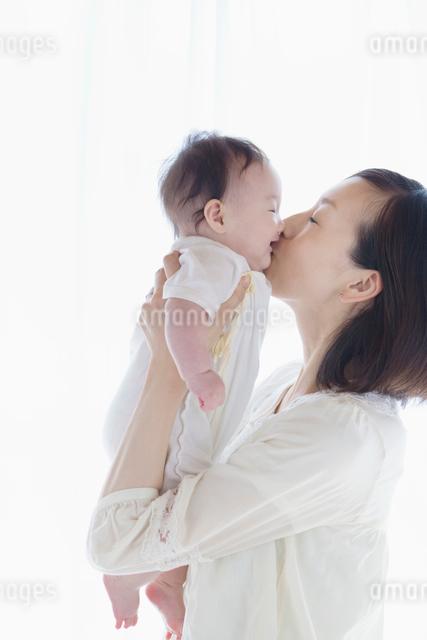 赤ちゃんにキスをする母親の写真素材 [FYI01571554]