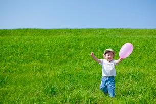 草原で風船を持った日本人の男の子の写真素材 [FYI01571623]