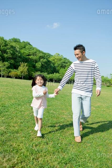 公園で手を繋いで歩く父と娘の写真素材 [FYI01571626]