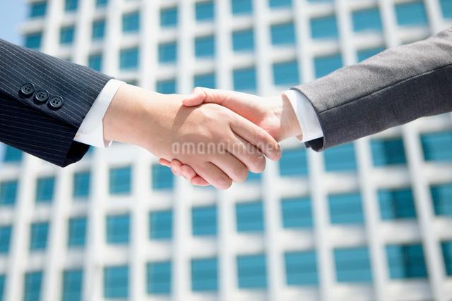 ビルの前で握手をする手の写真素材 [FYI01571705]