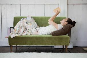 ソファで読書をする日本人女性の写真素材 [FYI01571766]