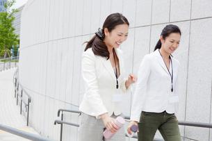 タンブラーを持って歩く2人のビジネスウーマンの写真素材 [FYI01571850]