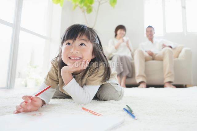 リビングでお絵描きをする娘とソファに座る両親の写真素材 [FYI01571859]