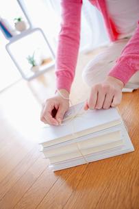 本を紐で結ぶ日本人女性の手元の写真素材 [FYI01571885]