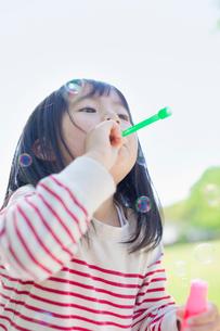 シャボン玉で遊ぶ女の子の写真素材 [FYI01571908]