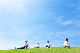 草原に座る日本人家族の写真素材 [FYI01571921]