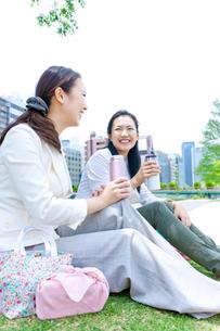 タンブラーを持って芝生に座る2人の女性の写真素材 [FYI01571922]