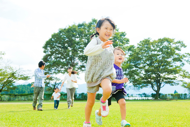 芝生を走る日本人の家族の写真素材 [FYI01571928]