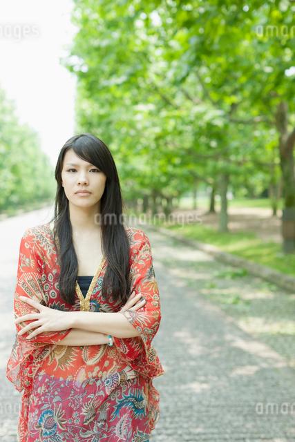 新緑の並木で腕を組む日本人女性の写真素材 [FYI01572076]