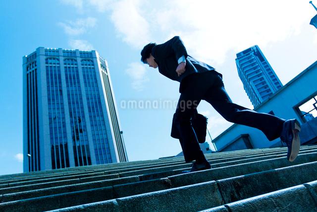 階段を駆け上る日本人ビジネスマンの写真素材 [FYI01572130]
