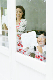 窓拭きをする日本人の母と娘の写真素材 [FYI01572246]