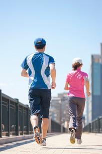 ジョギングをする日本人カップルの後ろ姿の写真素材 [FYI01572254]
