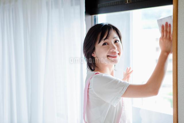 窓を拭く日本人女性の写真素材 [FYI01572266]