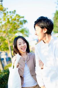 エコバックを持ち腕を組んで歩くカップルの写真素材 [FYI01572296]