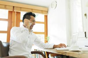 電話をしながらパソコンをする日本人の男性の写真素材 [FYI01572417]