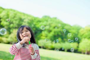 シャボン玉で遊ぶ女の子の写真素材 [FYI01572422]